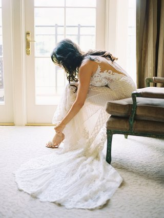 bride-in-beaded-wedding-dress-illusion-low-back-putting-on-heels-train-armchair