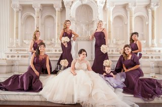 bride-in-white-and-gold-ball-gown-with-six-bridesmaids-in-long-purple-bridesmaid-dresses