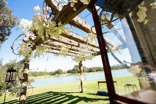 wood-arbor-at-ceremony-with-white-flowers-and-chandelier