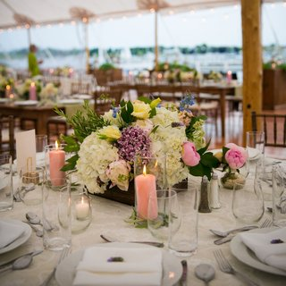 centerpieces-with-pink-peonies-purple-white-blue-and-yellow-flowers-peach-candles-in-hurricanes