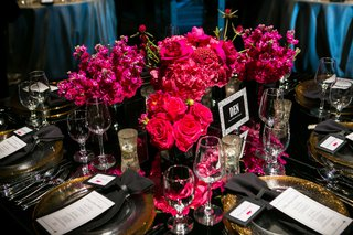low-centerpiece-with-bright-pink-hot-pink-flowers-on-black-table-decorations-gold-plates