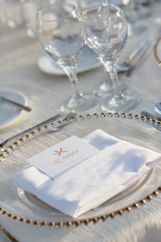 beach-wedding-reception-place-setting-with-clear-charger-seating-card-with-pink-starfish