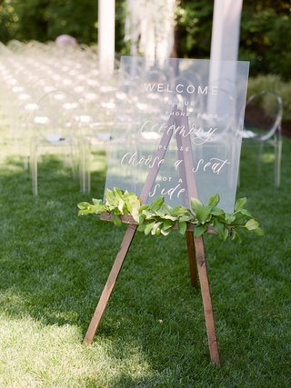 lucite-ceremony-sign-with-garland-of-greenery-on-wooden-easel-cell-phone-free-wedding