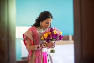 indian-bride-in-a-gold-fuchsia-sari-holds-a-bouquet-of-yellow-roses-calla-lilies-and-pink-orchids
