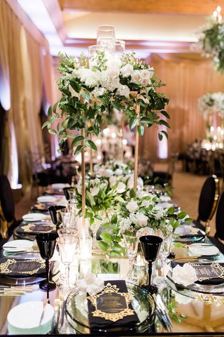 gold-stand-on-wedding-table-white-rose-hydrangea-greenery-candles-tulip-black-goblet-chairs-menus