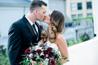 bride-in-strapless-wedding-dress-kissing-groom-hair-in-curls-burgundy-and-greenery-bouquet