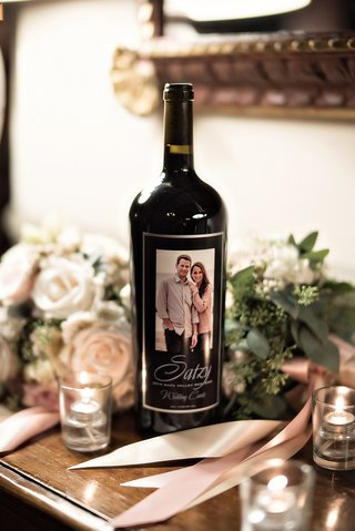 personalized-wine-bottle-on-display-at-wedding-with-engagement-photo-as-label