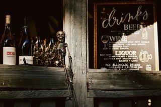 halloween-theme-wedding-reception-chalkboard-drink-menu-skeleton-on-bar-ledge-wood