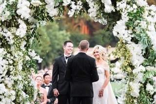 vow-exchange-under-flower-arch-greenery-orchids-groom-in-bow-tie-back-of-officiant