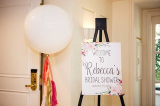 wedding-ideas-bridal-shower-sign-on-easel-large-white-balloon-with-gold-pink-red-orange-tassels