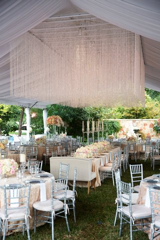 wedding-reception-green-grass-tent-crystal-installation-flowers-silver-chairs-settees-candelabra