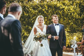 bride-in-stella-york-wedding-dress-on-arm-of-her-father-in-suit