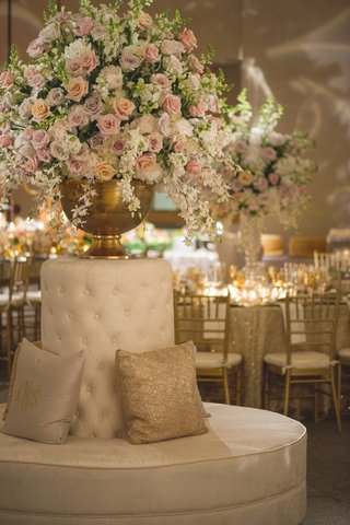 wedding-reception-with-round-sofa-glittery-throw-pillow-gold-urn-with-orchids-roses-snapdragons