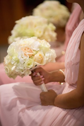 bridesmaids-in-pale-pink-dresses-hold-bouquets-of-white-hydrangreas-roses-lisianthus-peach-roses