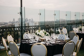 rooftop-wedding-reception-grey-tufted-chair-cushions-with-gold-frames-black-linens