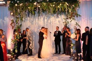 wedding ceremony chuppah jewish service purple blue delphinium flowers greenery arch industrial