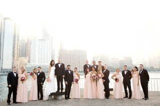 bridesmaids-in-long-blush-dresses-with-burgundy-bouquets-groomsmen-bride-groom-in-chicago-skyline