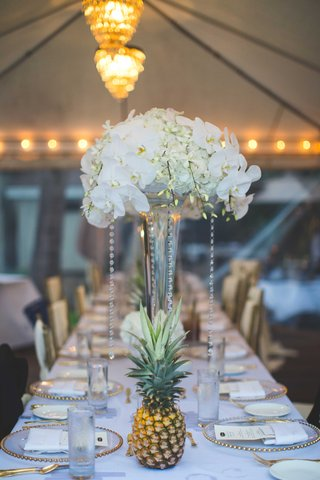 tall-white-centerpiece-with-crystals-orchid-hydrangea-freesia-blooms-gold-beaded-charger-plates-long