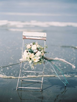 a-bouquet-of-white-and-green-with-blue-ribbons-on-an-old-wooden-chair-on-the-beach