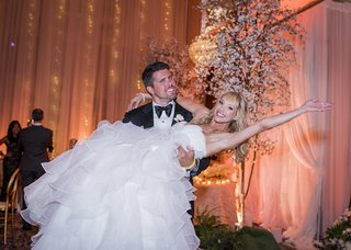 groom-in-tuxedo-lifting-up-bride-in-wedding-dress-ball-gown-with-full-layered-skirt