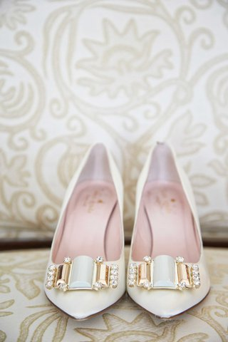 pointed-toe-kate-spade-shoes-with-gold-rhinestone-white-buckle-on-couch-at-ritz-carlton-hotel
