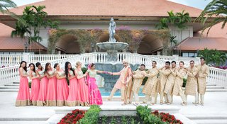 indian-american-wedding-party-in-traditional-attire-pretend-to-pull-bride-and-groom-apart