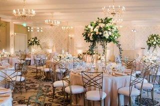 wedding-reception-ballroom-wallpaper-chandeliers-crisscross-chairs-tall-centerpiece-greenery-pink