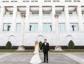bride-in-ines-di-santo-wedding-dress-holding-bouquet-and-hand-of-groom-with-tuxedo-bow-tie
