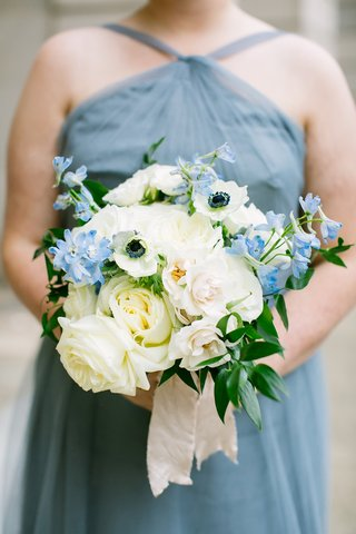 bridesmaid-in-blue-dress-holding-white-rose-anemone-blue-flower-greenery-bouquet-with-ribbon-wrap