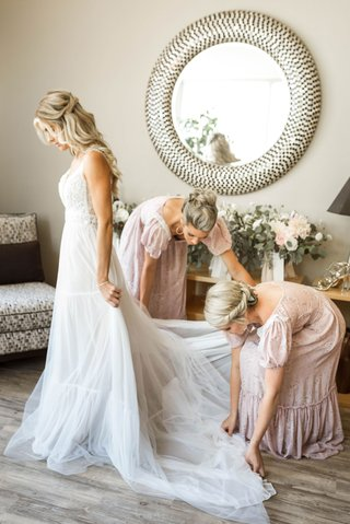 bridesmaids-in-vintage-puff-sleeve-bridesmaid-dresses-helping-bride-into-boho-wedding-dress