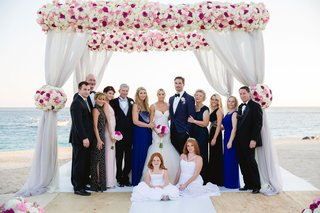 barbie-blank-and-sheldon-souray-under-wedding-arch-with-friends-and-family-on-beach-in-mexico