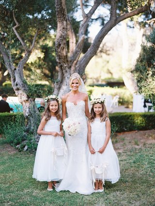 the-bride-standing-with-her-young-flower-girls-in-matching-white-dresses-and-flower-crowns-baskets
