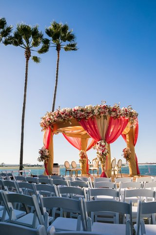 wedding-ceremony-facing-ocean-indian-wedding-mandap-gold-red-drapery-white-pink-flowers