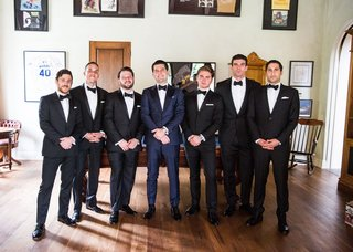groom-in-navy-suit-and-groomsmen-in-black-white-tuxedos-bow-ties-in-man-cave-pool-table-sports