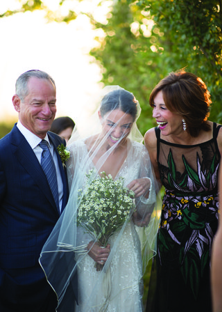 bride-with-blusher-veil-laughing-with-her-parents-before-walking-down-the-aisle