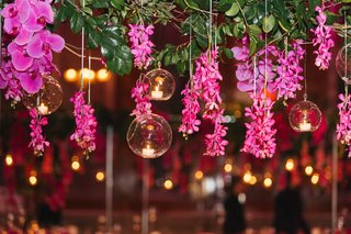 cascading-orchids-and-greenery-on-tall-trellis-like-wedding-table-arrangement