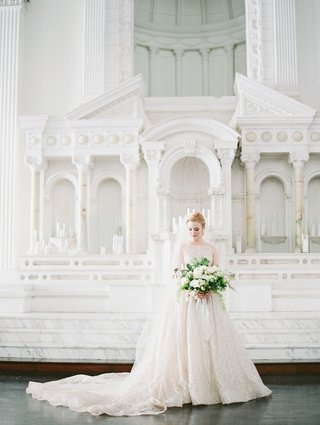 bride-at-vibiana-altar-in-boat-neck-wedding-dress-lazaro-cathedral-veil-greenery-white-flowers