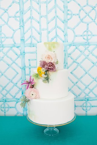 white-fondant-wedding-cake-three-layer-cascading-fresh-flowers-yellow-purple-pink-green-paint
