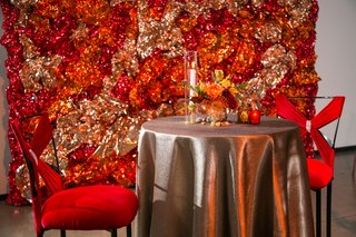 sweetheart-table-with-red-chairs-backdrop-of-foil-made-to-look-like-fire