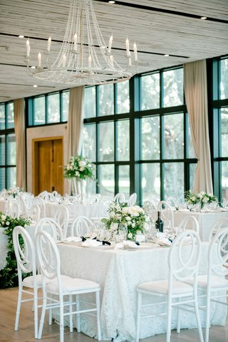 wedding-reception-floor-to-ceiling-black-frame-windows-wood-door-white-table-chairs-high-low-flowers