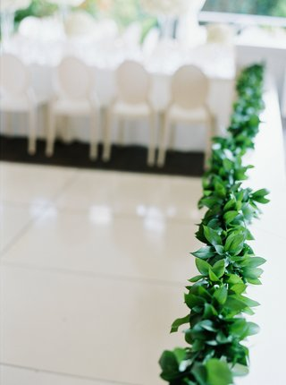 garland-of-greenery-lining-the-border-of-the-wedding-reception-tent
