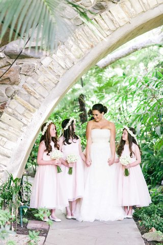 bride-holding-hands-with-flower-girls-in-light-pink-tea-length-dresses-with-white-flower-crowns