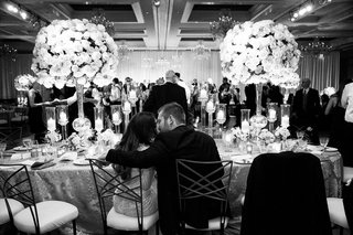 black-and-white-photo-of-bride-and-groom-kissing-at-head-table-guests-on-dance-floor
