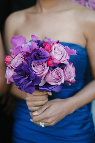 bridesmaid-in-blue-dress-holding-purple-and-pink-roses