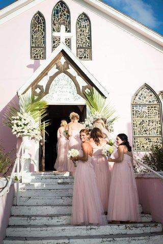 bridesmaids-in-light-pink-blush-bridesmaid-dresses-walking-up-stairs-into-light-pink-church-bahamas