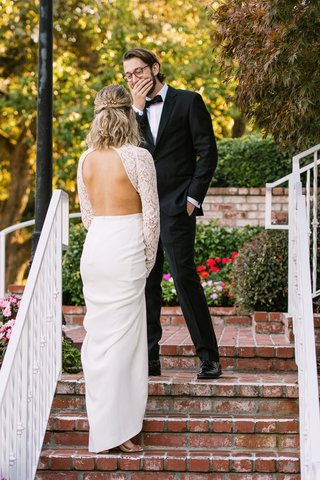 grooms-cute-reaction-to-first-look-bride-in-open-back-wedding-dress-lace-long-sleeves-crepe-skirt
