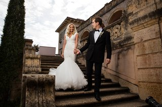 groom-in-tuxedo-leading-bride-in-mermaid-berta-wedding-dress-down-stairs