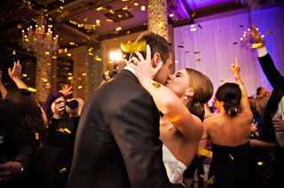 bride-and-groom-kiss-at-reception-while-gold-confetti-falls-around-them-on-the-dance-floor