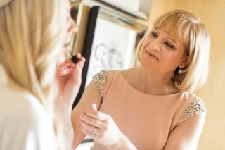 bride-in-white-robe-getting-lip-gloss-put-on-by-mother-of-bride-in-peach-dress-crystal-shoulder