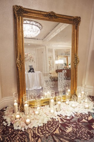 wedding-reception-seating-chart-gold-frame-mirror-white-calligraphy-hurricane-candle-white-pink